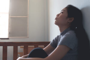 Asian woman leaning against wall in distress. She is feeling out of her head because of the trauma she has been experiencing. If you can relate to the frustration and overwhelm of dealing with ptsd in chesapeake, va. Try getting treating ptsd in chesapeake, va or richmond, va. We are here to help you get through this difficult time. Whole wellness journey is ready to help you move forward with ptsd therapy and trauma treatment in richmond, va
